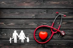 Diagnóstico y curación de la enfermedad cardiaca con las figuras de papel del estetoscopio y de la familia en maqueta de madera d foto de archivo