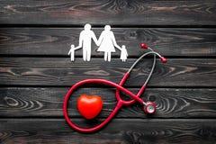 Diagn?stico y curaci?n de la enfermedad cardiaca con las figuras de papel del estetoscopio y de la familia en la opini?n superior foto de archivo libre de regalías
