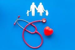 Diagn?stico y curaci?n de la enfermedad cardiaca con las figuras de papel del estetoscopio y de la familia en la opini?n superior fotos de archivo