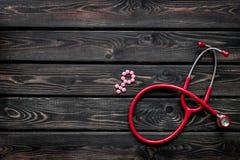 Diagnóstico y curación de la enfermedad ginecológica con el estetoscopio y del símbolo femenino en maqueta de madera de la opinió foto de archivo