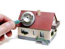 Diagnósticos de la casa. Casa modelo con la mano y el estetoscopio Imagenes de archivo