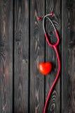 Diagn?stico y curaci?n de la enfermedad cardiaca con el estetoscopio y del coraz?n en maqueta de madera de la opini?n superior de foto de archivo