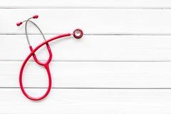 Diagn?stico y curaci?n de la enfermedad cardiaca con el estetoscopio en la maqueta de madera blanca de la opini?n de top del fond imágenes de archivo libres de regalías