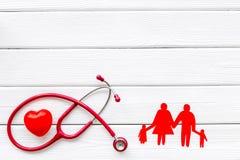 Diagn?stico y curaci?n de la enfermedad cardiaca con las figuras de papel del estetoscopio y de la familia en la maqueta blanca d fotografía de archivo