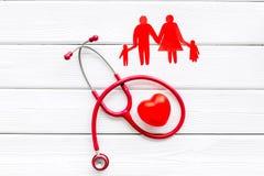 Diagn?stico y curaci?n de la enfermedad cardiaca con las figuras de papel del estetoscopio y de la familia en la opini?n superior imagenes de archivo