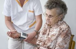 Diagnose. Measuring the blood pressure of the eldely woman Royalty Free Stock Photos