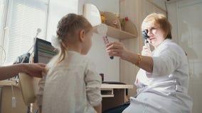Diagnose in Kind-` s Augenheilkunde - kleines Mädchen der Optometrikerdiagnose stockbild