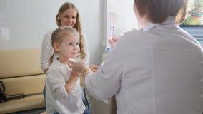 Diagnose in Kind-` s Augenheilkunde - kleines Mädchen der Optometrikerdiagnose lizenzfreies stockbild