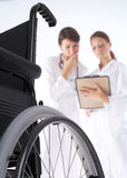 Diagnosis. Two women doctors are looking at the card of the patient and a wheelchair is in the frond Stock Images