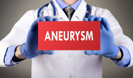 Diagnosis aneurysm. Doctor`s hands in blue gloves shows the word aneurysm. Doctor in gloves on grey background. Medical concept royalty free stock photography