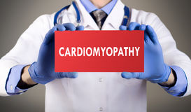 Diagnosis cardiomyopathy. Doctor`s hands in blue gloves shows the word cardiomyopathy. Doctor in gloves on grey background. Medical concept royalty free stock images