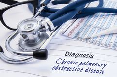 Diagnosis of Chronic pulmonary obstructive disease COPD. On doctors table lies paper with title Chronic pulmonary obstructive di. Sease surrounded by stethoscope stock image