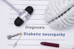 Diagnosis of Diabetic neuropathy. Neurological hammer and brain figure lie on a medical  paper form with a heading diagnosis of Di royalty free stock photography