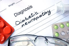 Diagnosis Diabetic neuropathy and tablets. Diagnosis Diabetic neuropathy and tablets on a wooden table royalty free stock images