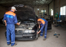Diagnosis of engine. Two men mechanic in uniform examining car at the auto repair shop. Diagnosis of engine royalty free stock photography
