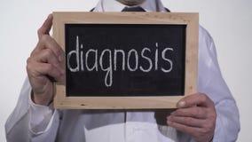 Diagnosis escrita en la pizarra en las manos del terapeuta, servicios de diagnóstico de la medicina almacen de metraje de vídeo