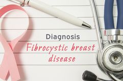 Diagnosis Fibrocystic breast disease. Pink ribbon as symbol of struggle with breast oncology and disorders and stethoscope lying o. N medical form with text royalty free stock photo