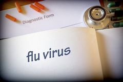 Diagnosis flu virus written in the diagnostic form and pills royalty free stock photo