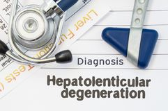 Diagnosis Hepatolenticular Degeneration. Neurological hammer, stethoscope and liver laboratory test lie on note with title of Hep. Atolenticular Degeneration royalty free stock image