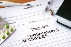 Diagnosis Huntingtons disease and tablets on a wooden table. Royalty Free Stock Images