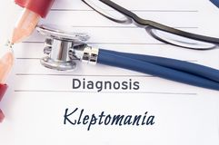 Diagnosis Kleptomania. Psychiatric diagnosis Kleptomania is written on paper, on which lay stethoscope and hourglass for measuring stock photography