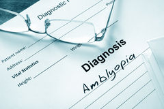 Diagnosis list with Amblyopia and glasses. Eye disorder concept royalty free stock photography