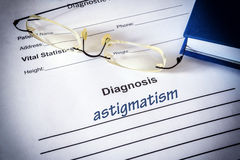 Diagnosis list with Astigmatism and glasses. Eye disorder concept stock photography