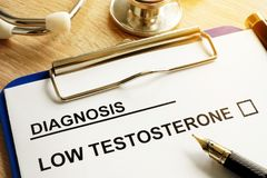 Diagnosis Low testosterone on a desk. Diagnosis Low testosterone and pen on a desk royalty free stock photography
