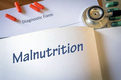 Diagnosis malnutrition written in the diagnostic. Form and pills Royalty Free Stock Photo
