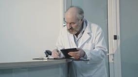Diagnosis mayor de la escritura del doctor en el mostrador de recepción 4K almacen de video