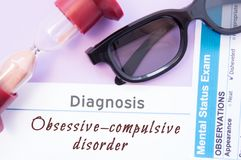 Diagnosis of Obsessive Compulsive Disorder. Hourglass, doctor glasses, mental status exam are near inscription Obsessive-Compulsiv. E. Causes, symptoms Royalty Free Stock Image