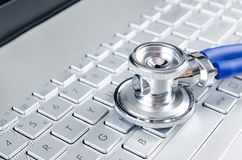 Diagnosis and repair of computers. Stethoscope on laptop stock photo