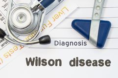 Diagnosis Wilson Disease. Neurological hammer, stethoscope and liver laboratory test lie on note with title of Wilson Disease. Con stock images
