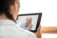 Free Diagnostic And Consultation With The Telemedicine, Doctor Holding A Tablet, Elderly Woman With Headache Royalty Free Stock Image - 118240966