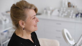 diagnostic Bonnes nouvelles portrait de femme supérieure de sourire dans le bureau du docteur banque de vidéos