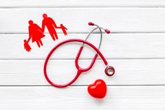 Diagnostic and cure of cardiac disease with stethoscope and family paper figures on white background top view. Family doctor. Cardiologist. Diagnostic and cure stock image