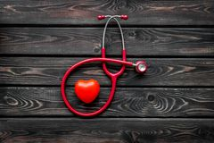 Diagnostic and cure of cardiac disease with stethoscope and heart on wooden background top view. Family doctor. Cardiologist. Diagnostic and cure of cardiac stock photo