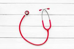 Diagnostic and cure of cardiac disease with stethoscope on white wooden background top view mock-up. Family doctor. Cardiologist. Diagnostic and cure of cardiac stock photography