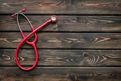 Diagnostic and cure of cardiac disease with stethoscope on wooden background top view mock-up. Family doctor. Cardiologist. Diagnostic and cure of cardiac stock image