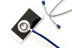 Diagnostic of gadgets on white background with stethoscope.  Royalty Free Stock Image