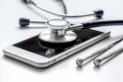 Diagnostic of gadgets on white background with stethoscope.  Stock Photo