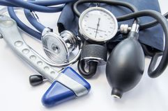 Diagnostic kit of neurologist or internal medicine doctor. Neurological reflex hammer, sphygmomanometer and stethoscope lying on w. Hite background. Diagnosis of stock image