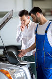 Diagnostic problem. On car, looking at laptop royalty free stock photo