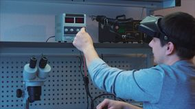 Diagnostics of electronic components. The engineer uses special equipment. Connects negative black and positive red wires to the device stock video footage