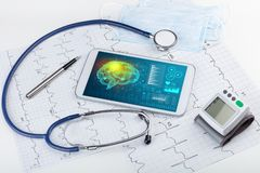 Diagnostics on tablet with brain functionality concept. Brain functionality report with medical devices aroundn stock images