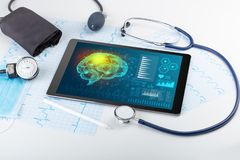 Diagnostics on tablet with brain functionality concept. Brain functionality report with medical devices aroundn stock image