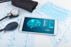 Diagnostics on tablet with brain functionality concept. Brain functionality report with medical devices around royalty free stock photography