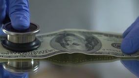 Diagnostiek van dollar met stethoscoop, financiële markt controleconcept stock videobeelden