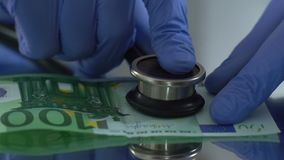 Diagnostiek van euro met stethoscoop, financiële markt controleconcept stock videobeelden