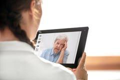 Diagnostik och konsultation med telemedicinen, doktorsholdin royaltyfri bild